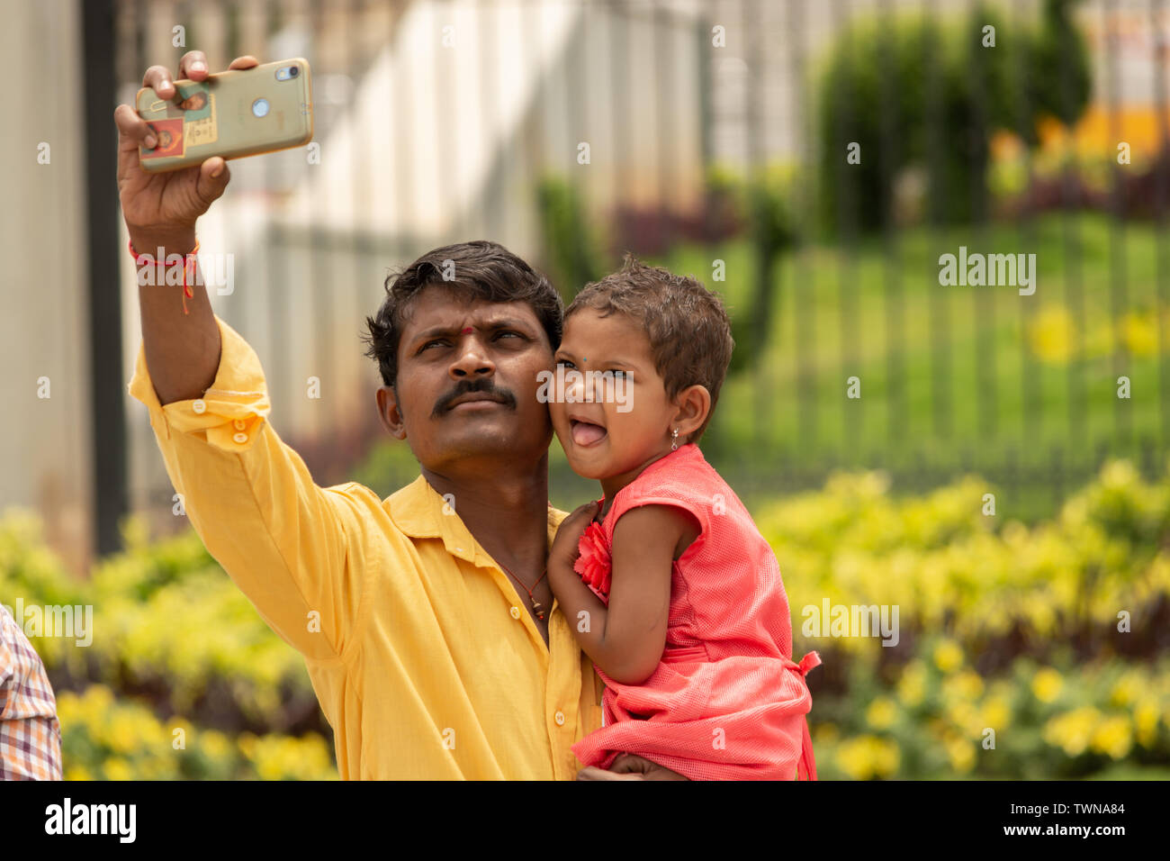Bangalore, Karnataka India-June 04 2019 : Father and little cute daughter taking picture or selfie with Mobile Phone or cellphone camera at tourist pl Stock Photo