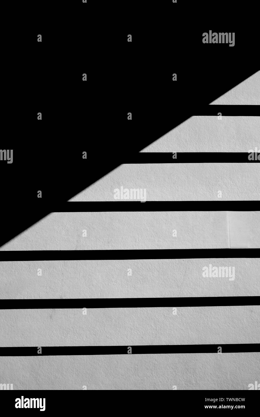 Black and white image of exterior house siding, with a strong shadow. - Stock Image