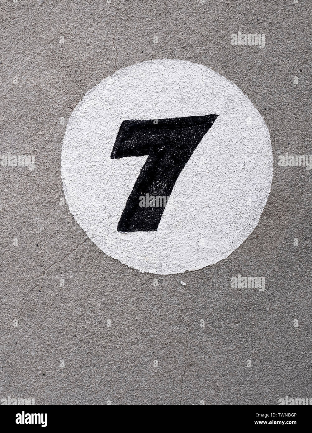 Painted number seven on a rendered wall - Stock Image