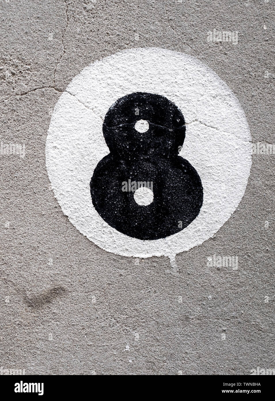 Painted number eight on a rendered wall - Stock Image