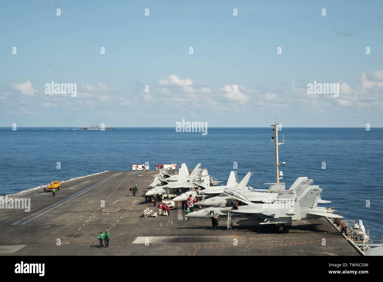 190619-N-JK118-1027 SOUTH CHINA SEA (June 19, 2019) Japan Maritime Self-Defense Force (JMSDF) ship JS Izumo (DH-183) sails in front of the Navy's forward-deployed aircraft carrier USS Ronald Reagan (CVN 76) during Reagan's flight operations. Ronald Reagan, the flagship of Carrier Strike Group 5, provides a combat-ready force that protects and defends the collective maritime interests of its allies and partners in the Indo-Pacific region. (U.S. Navy photo by Mass Communication Specialist Seaman Thomas Leishman) - Stock Image