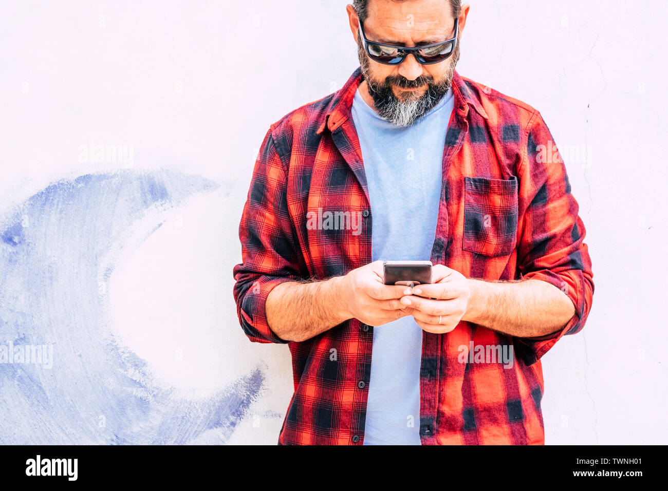 Coloured hipster people adult man with beard usgin modern cellular smart phone - standing on a white wall background - alternative job and work office Stock Photo
