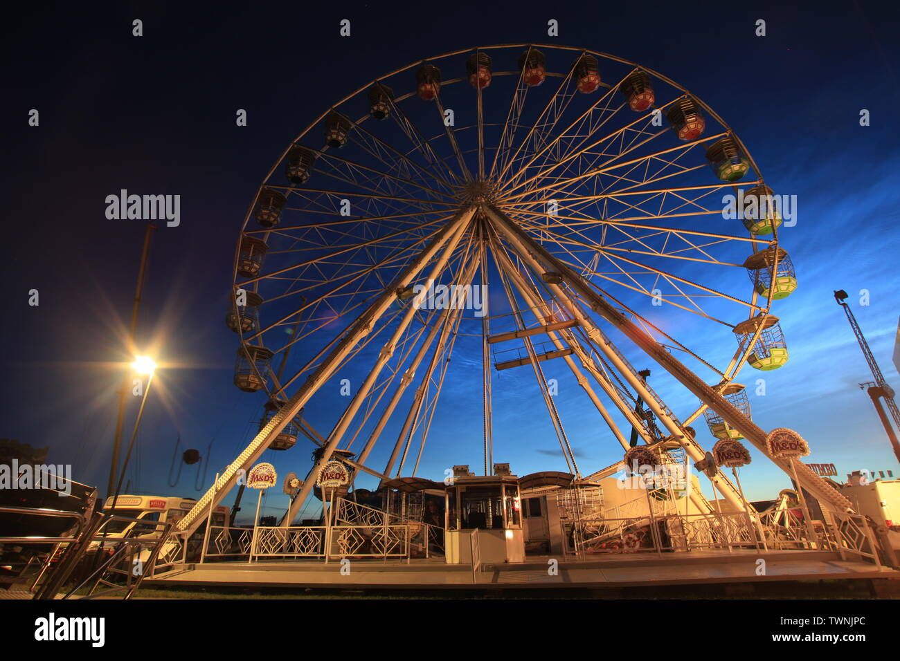 Newcastle upon Tyne, UK. 22th June, 2019. Noctilucent clouds with the hoppings funfair on town moor. Credit:David Whinham/Alamy Live News - Stock Image