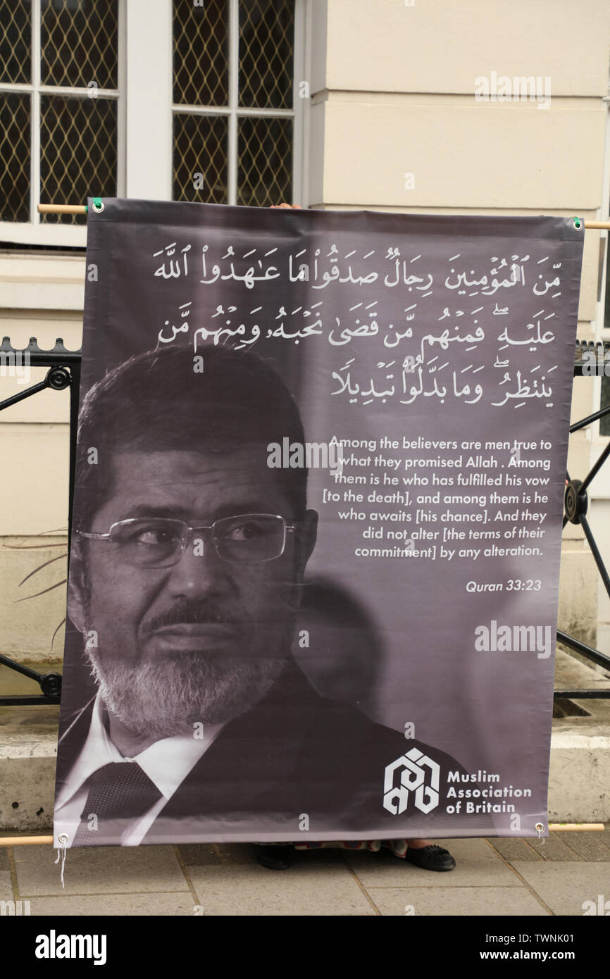 London, UK. 21st June 2019. Protester holds a large banner with a picture of Morsi and a quote from the Quran by the Muslim Association of Britain in front of the Egyptian embassy in London, in remembrance of Morsi, who recently collapsed in court in Cairo. Credit: Joe Kuis / Alamy News Stock Photo