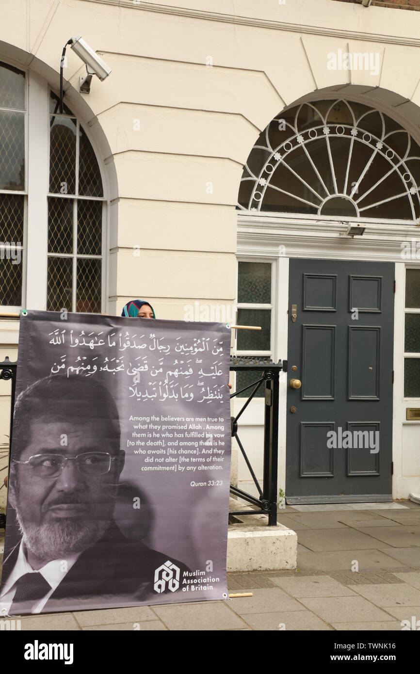 London, UK. 21st June 2019. Protester holds a large banner with a picture of Morsi and a quote from the Quran by the Muslim Association of Britain in front of the Egyptian embassy in London, in remembrance of Morsi, who recently collapsed in court in Cairo. Credit: Joe Kuis / Alamy News - Stock Image