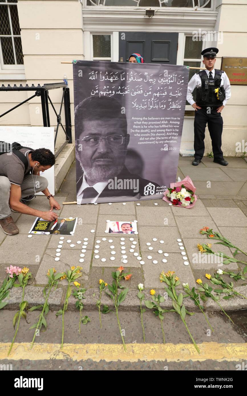 London, UK. 21st June 2019. Protesters lay candles and hold a large banner with a picture of Morsi and a quote from the Quran by the Muslim Association of Britain in front of the Egyptian embassy in London, in remembrance of Morsi, who recently collapsed in court in Cairo. Credit: Joe Kuis / Alamy News - Stock Image