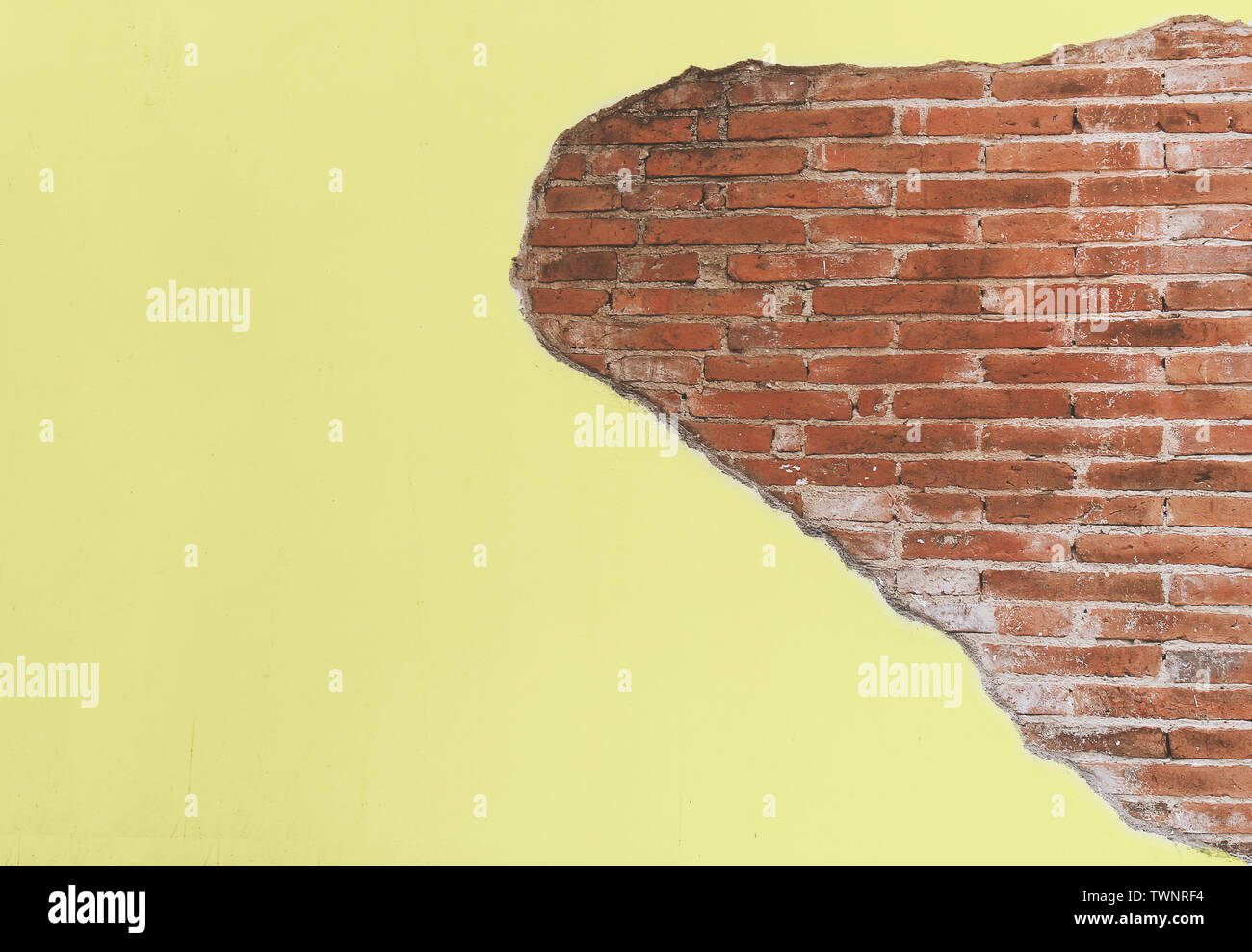 vintage old yellow crack cement wall with red brick block, antique wall for background Stock Photo