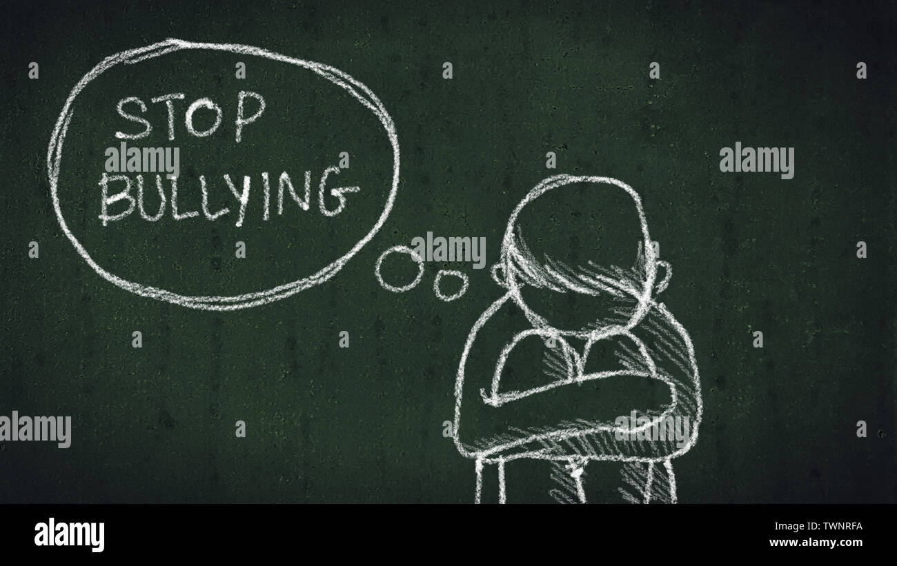 sad young boy sitting on the floor with text stop bullying written with chalk on chalkboard. social problems of humanity - Stock Image
