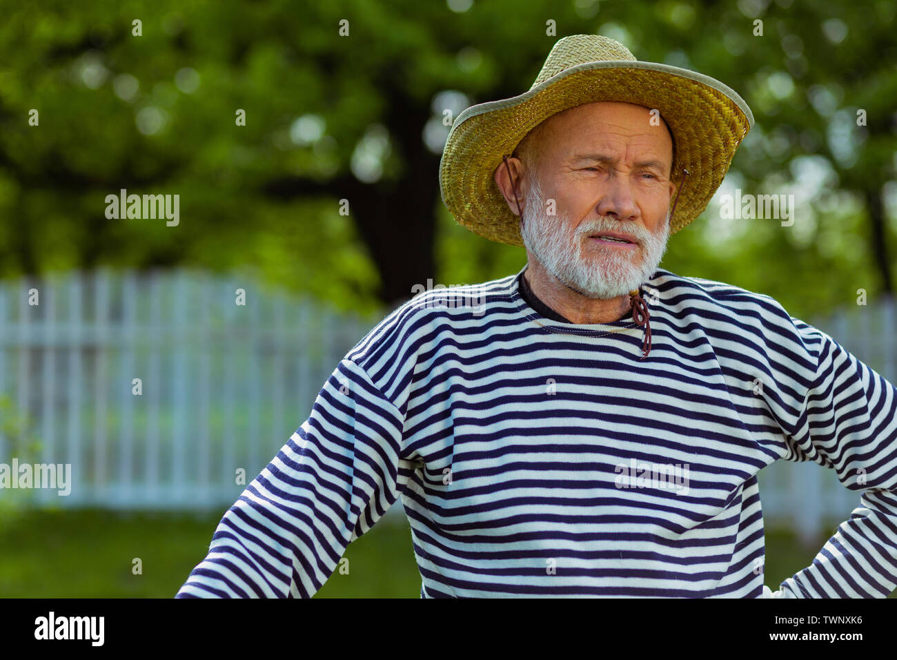 Man feeling tired. Grey-haired retired man in straw hat feeling tired after digging ground in garden - Stock Image
