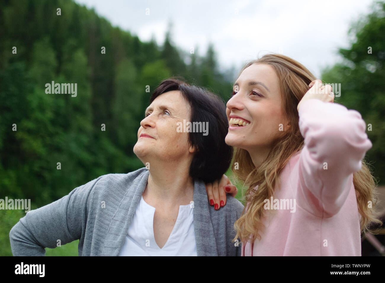 Happy mother and daughter traveling and posing together over landscape of forest and mountains - Stock Image