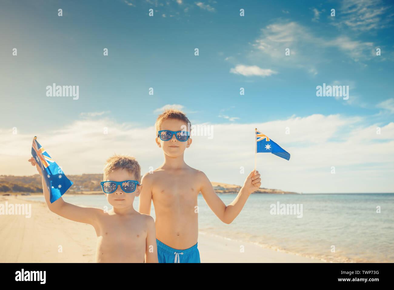 Kids holding Australian flags in hands on Australia day, Emu Bay, Kangaroo Island - Stock Image