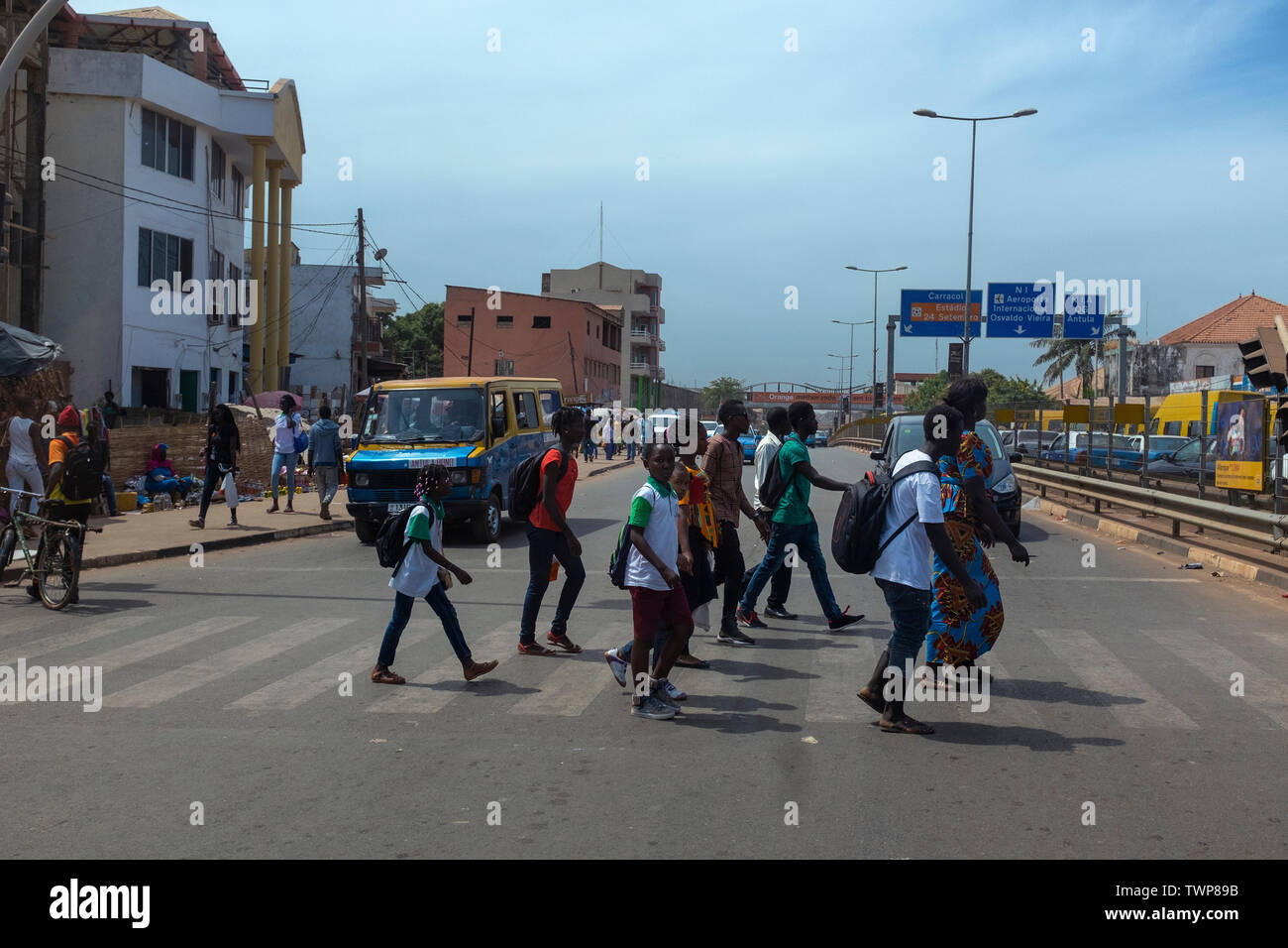 Bissau, Republic of Guinea-Bissau - February 8, 2018: Street scene in the city of Bissau with people crossing an avenue near the Bandim Market, in Gui - Stock Image