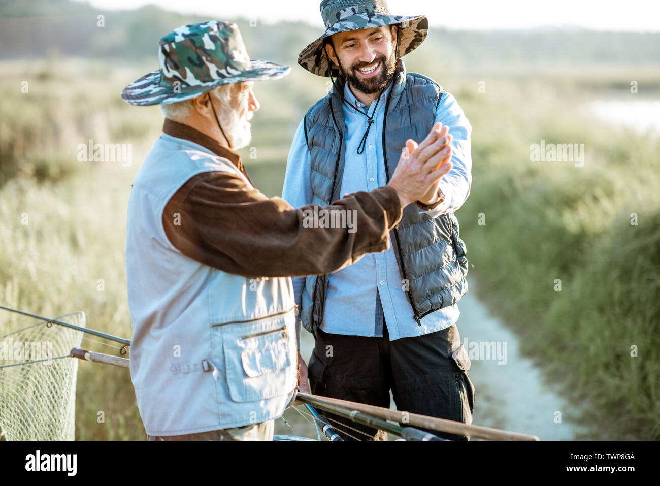 Grandfather with adult son giving a five each other, going back after the fishing outdoors - Stock Image