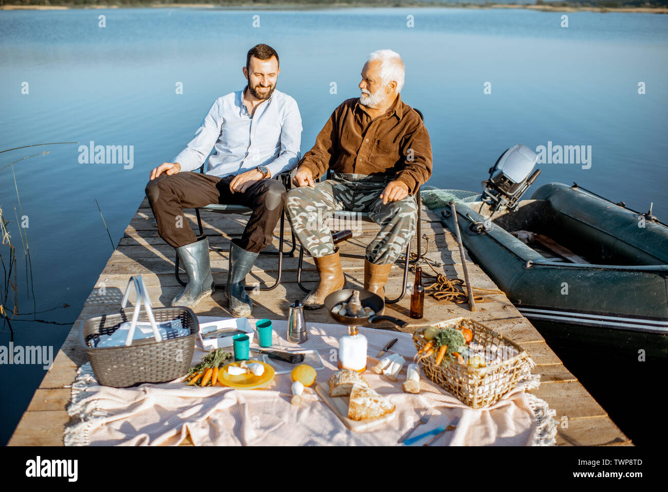 Grandfather with adult son having a picnic, sitting on the wooden pier after the fishing on the lake early in the morning - Stock Image