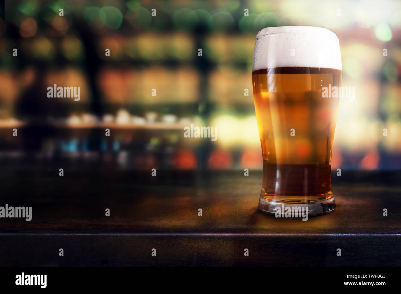 Glass of Beer on Table in Bar or Restaurant. Side View. Night Scene - Stock Image