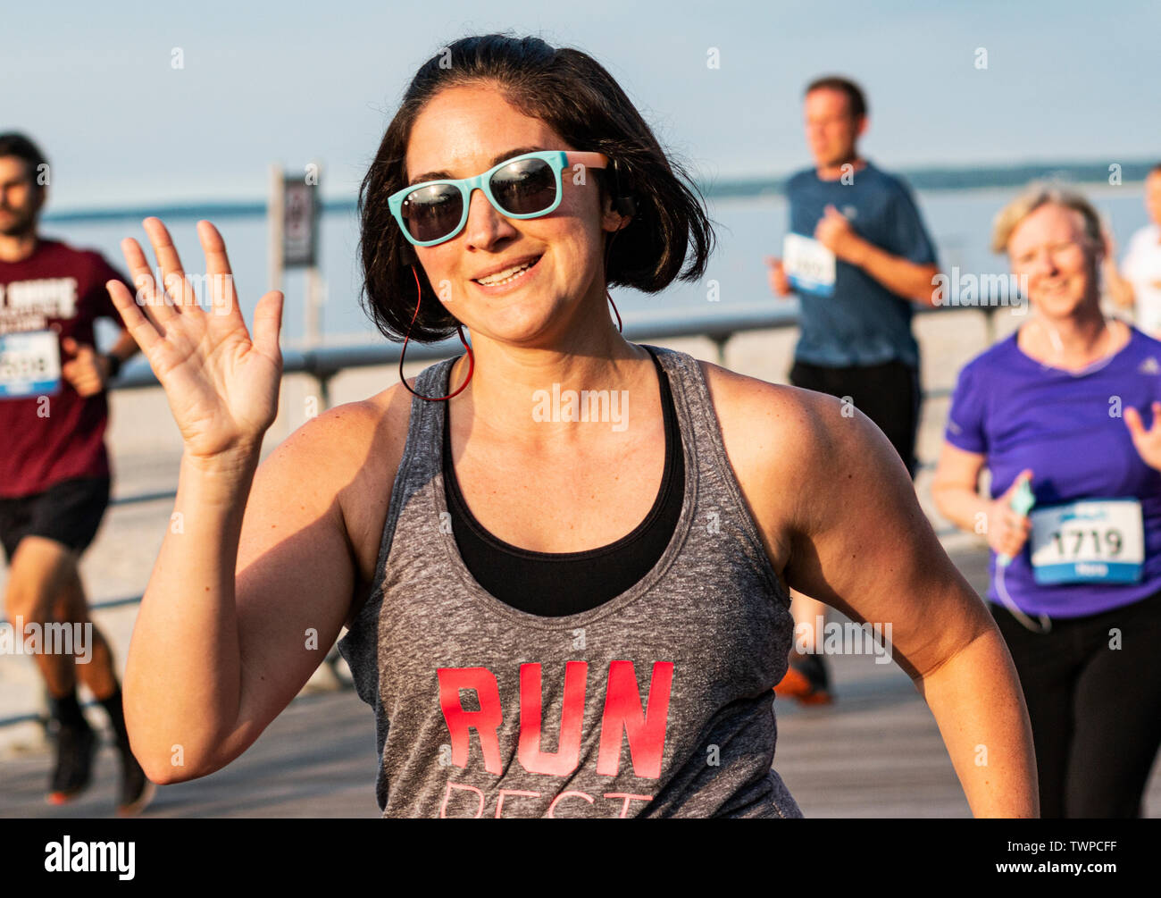 Kings Park, New York, USA - 17 June 2019: A women wearing aqua blue sunglasses waving and smiling at camera during a 10K running race the boardwalk at - Stock Image