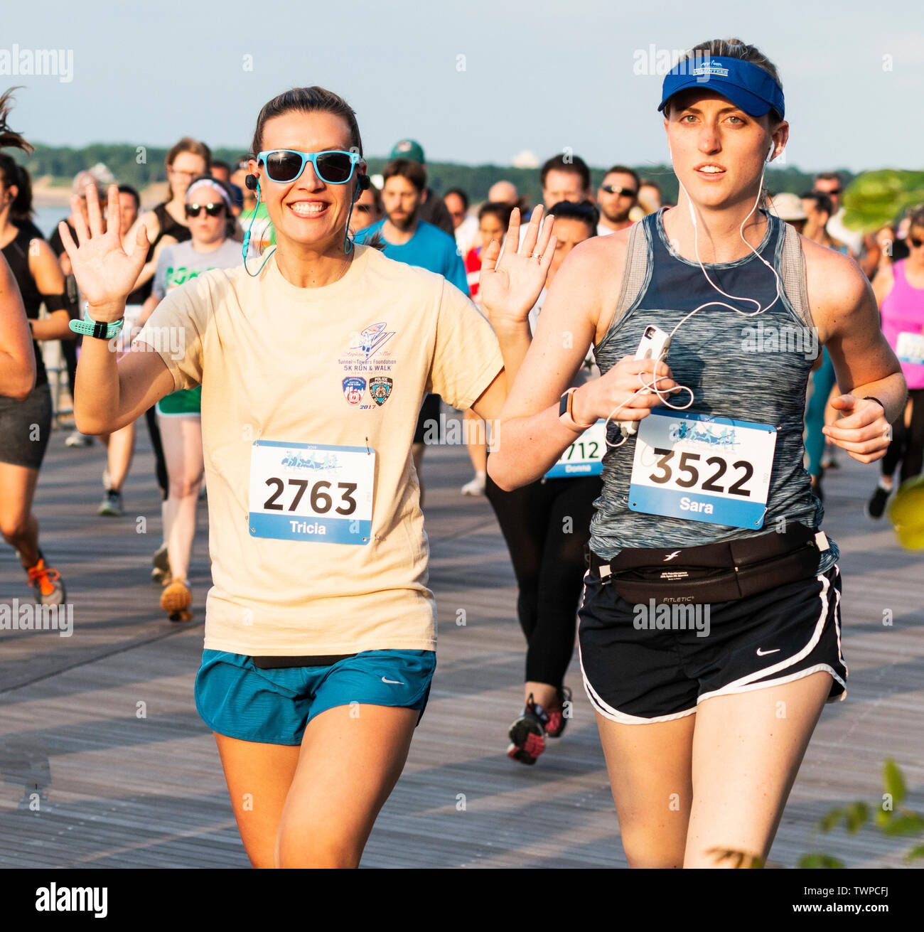 Kings Park, New York, USA - 17 June 2019: A happy female runner is waving at the camera during the 10K State Parks summer seiries running race at Sunk - Stock Image