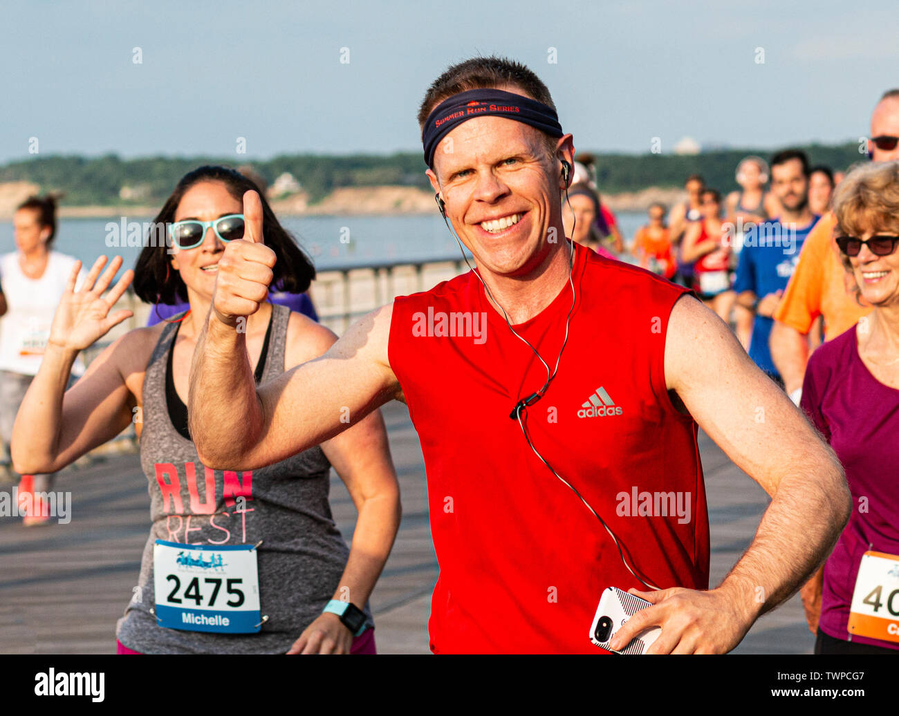 Kings Park, NEw York, USA - 17 June 2019: Runners smiling and waving to the camera during a 10K race on a boardwalk at the beach. - Stock Image