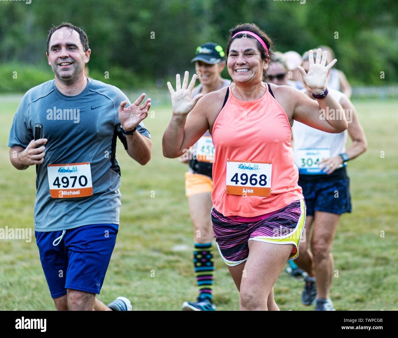 Kings Park, New York, USA - 17 June 2019: Excited runners waving to camera suring the New York State Parks summer seiries 10K run at Sunken Meadow. - Stock Image