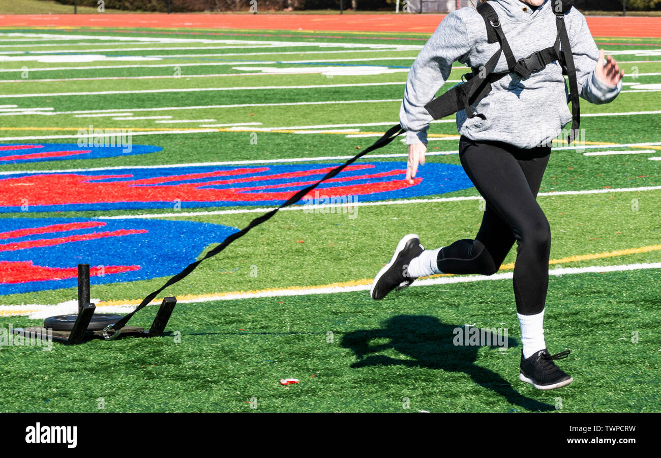 High school runner is pulling a sled with weight across a green turf field running toward the camera at track and field practice. - Stock Image