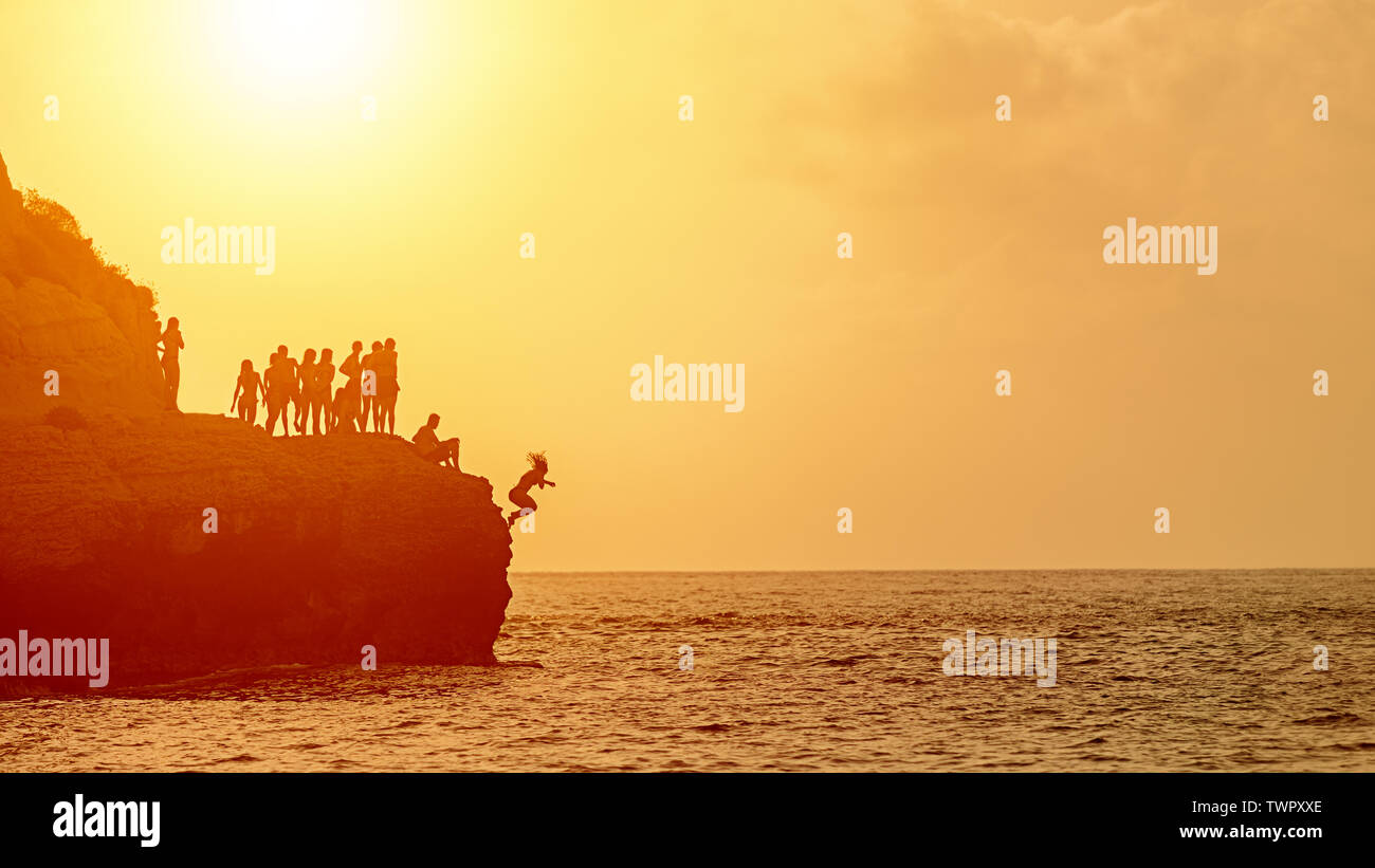 Summer fun with best friends cliff jumping into ocean – young people silhouette enjoying time together swimming at sunset and jump from rock into sea - Stock Image