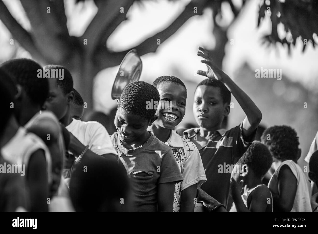 Children smiling and laughing while waiting in line for food - Stock Image
