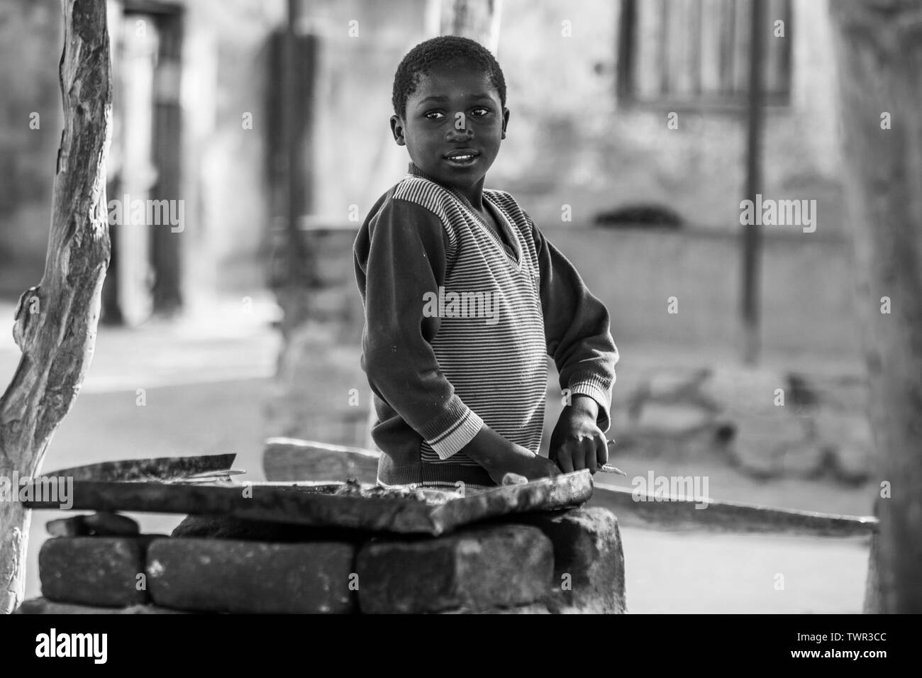 A child street vendor standing by his fryer waiting for customers - Stock Image