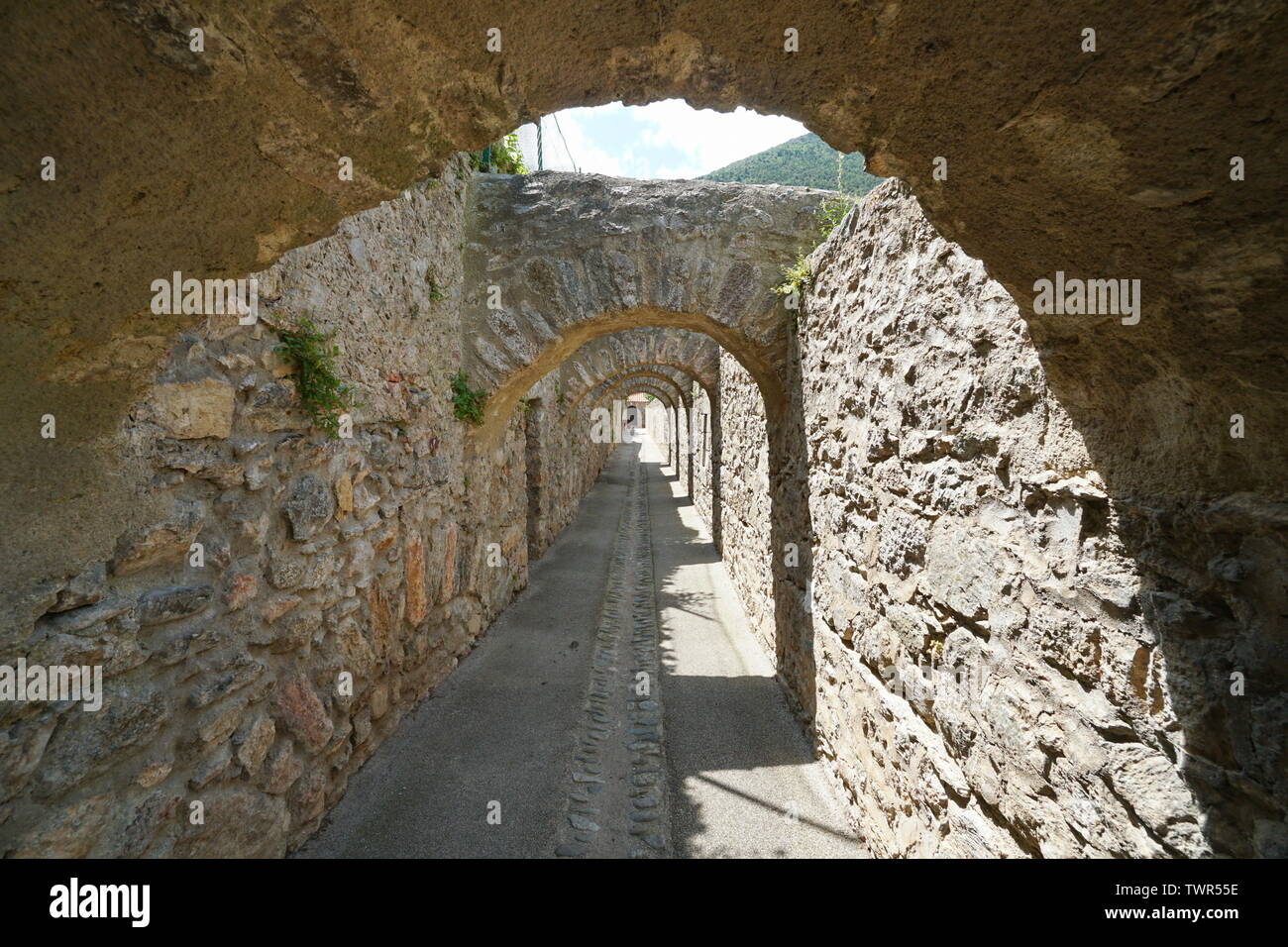 Passage under stone arches inside the fortified village of Villefranche de Conflent, Pyrenees Orientales, Occitanie, France Stock Photo