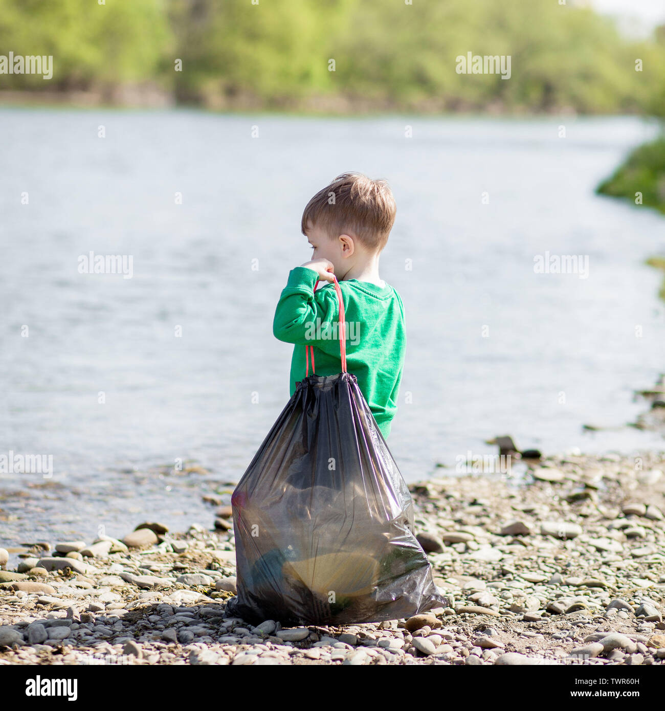 Save environment concept, a little boy collecting garbage and plastic bottles on the beach to dumped into the trash - Stock Image