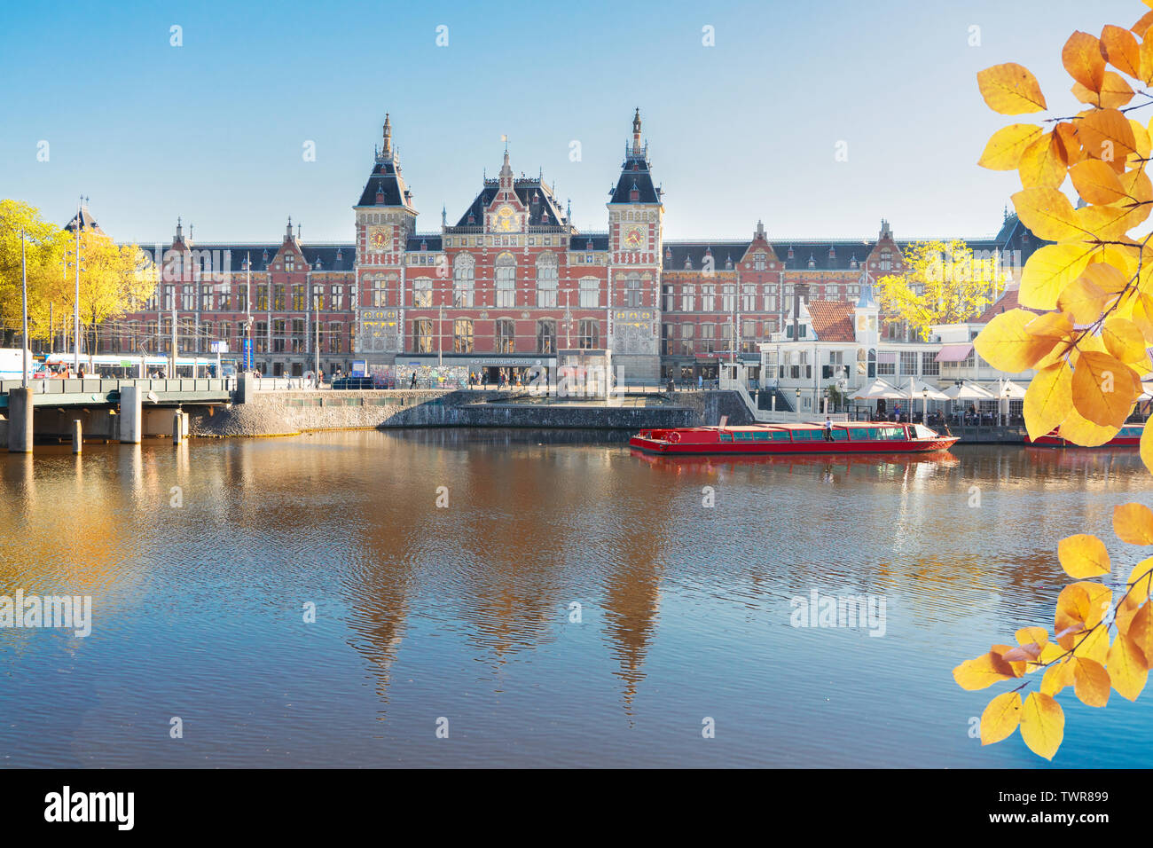 famous cityscape with central railway station and old town canal in Amsterdam, Holland at fall - Stock Image