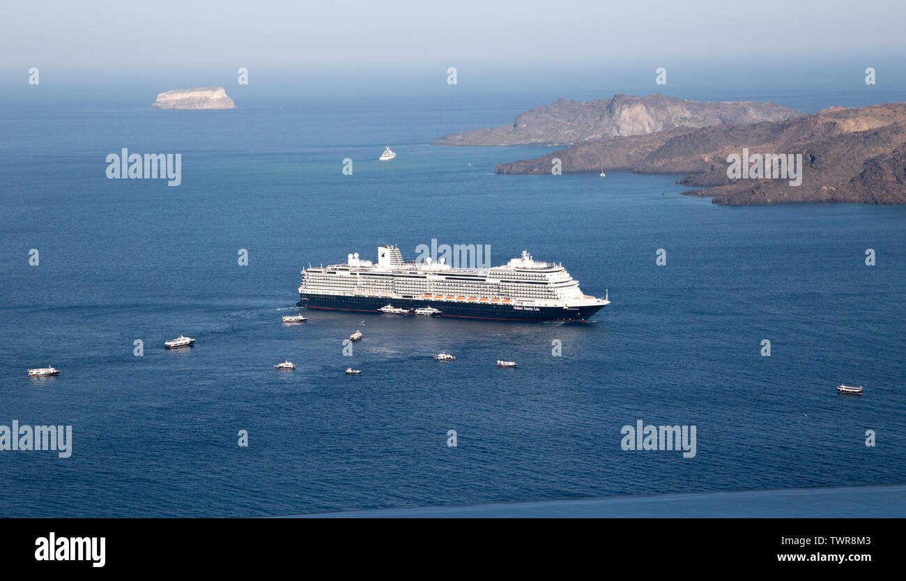 cruise ship sits off the coast of Santorini with small tenders services the passengers going ashore Stock Photo