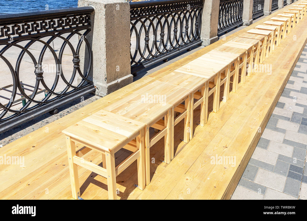 Wooden backless stools stand in a row on the city embankment - Stock Image