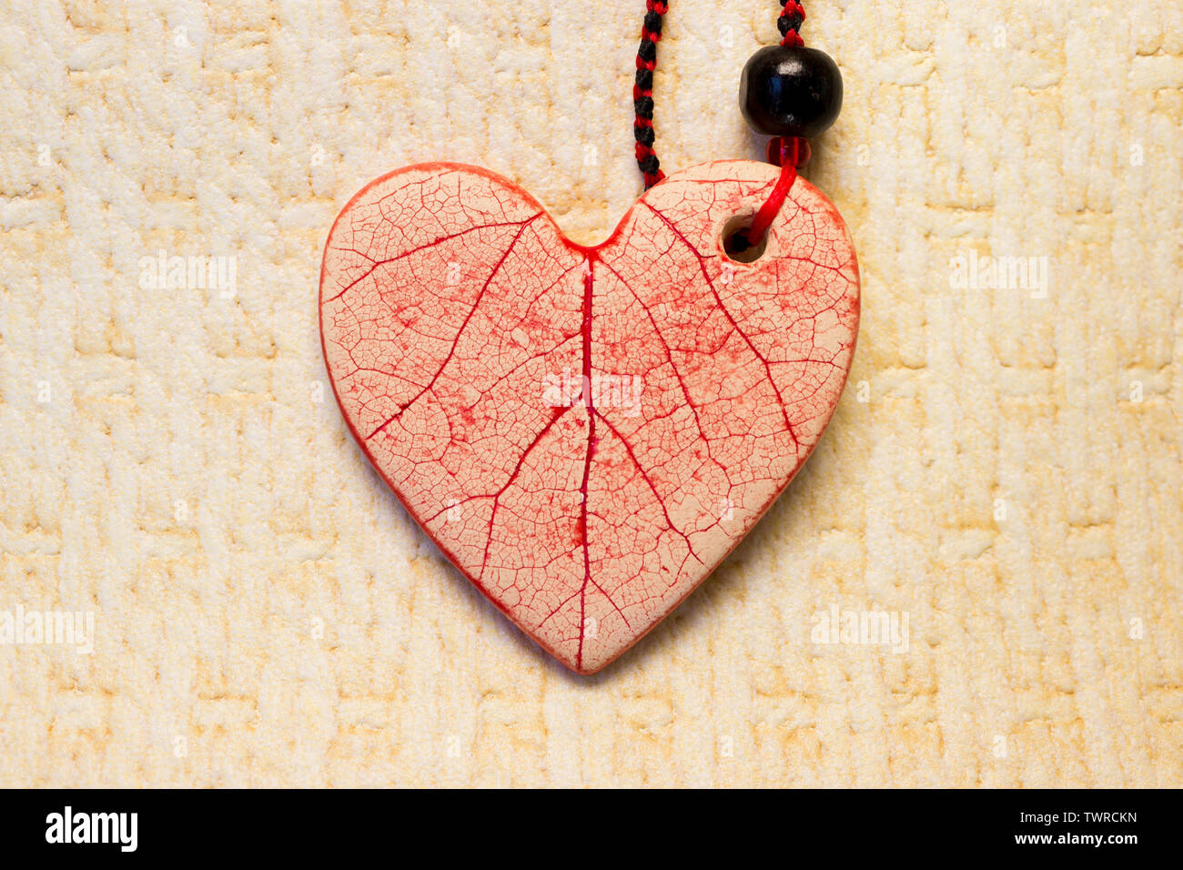one ceramic heart of white clay with red icing. pendant with beads and waxed thread Stock Photo