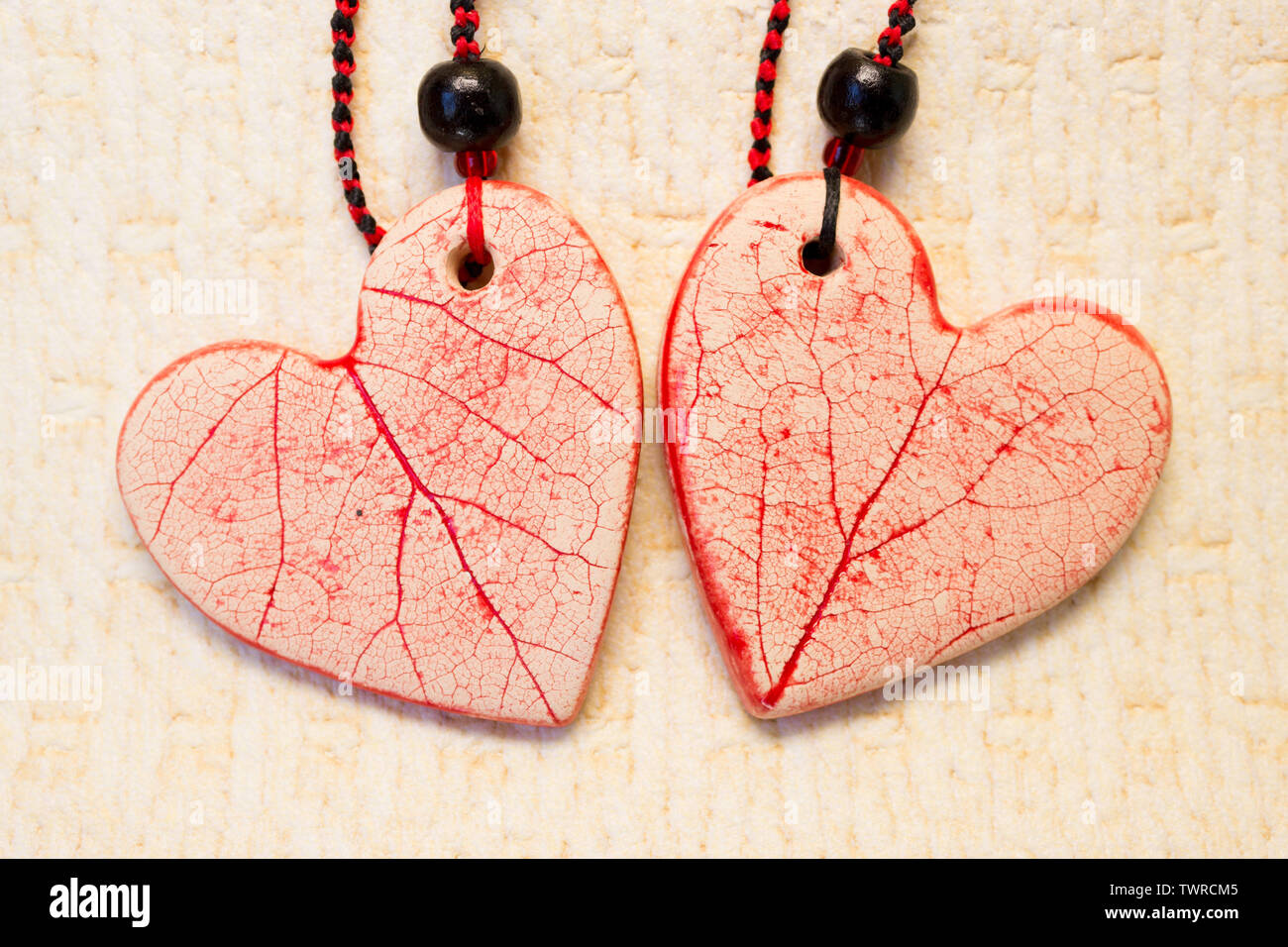 two ceramic hearts of white clay with red icing. pendant with beads and waxed thread. Stock Photo