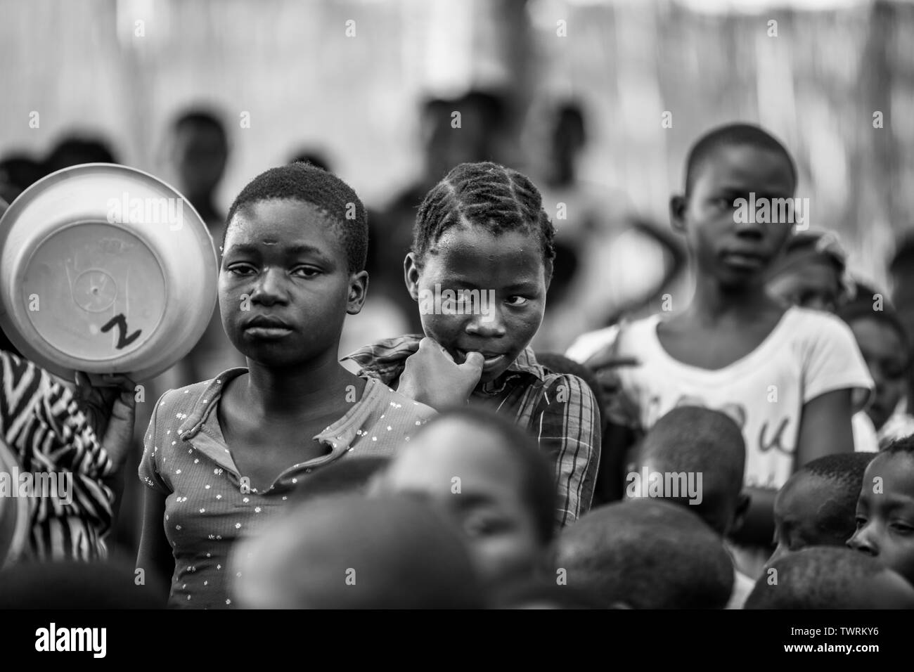 Black and White Photo of African girls waiting in line to get food to eat - Stock Image