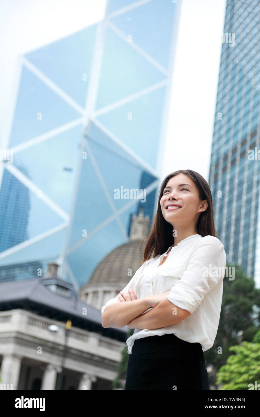Asian business woman confident outdoor in Hong Kong standing proud in suit cross-armed in business district. Young mixed race female Chinese Asian / Caucasian female professional in central Hong Kong. Stock Photo