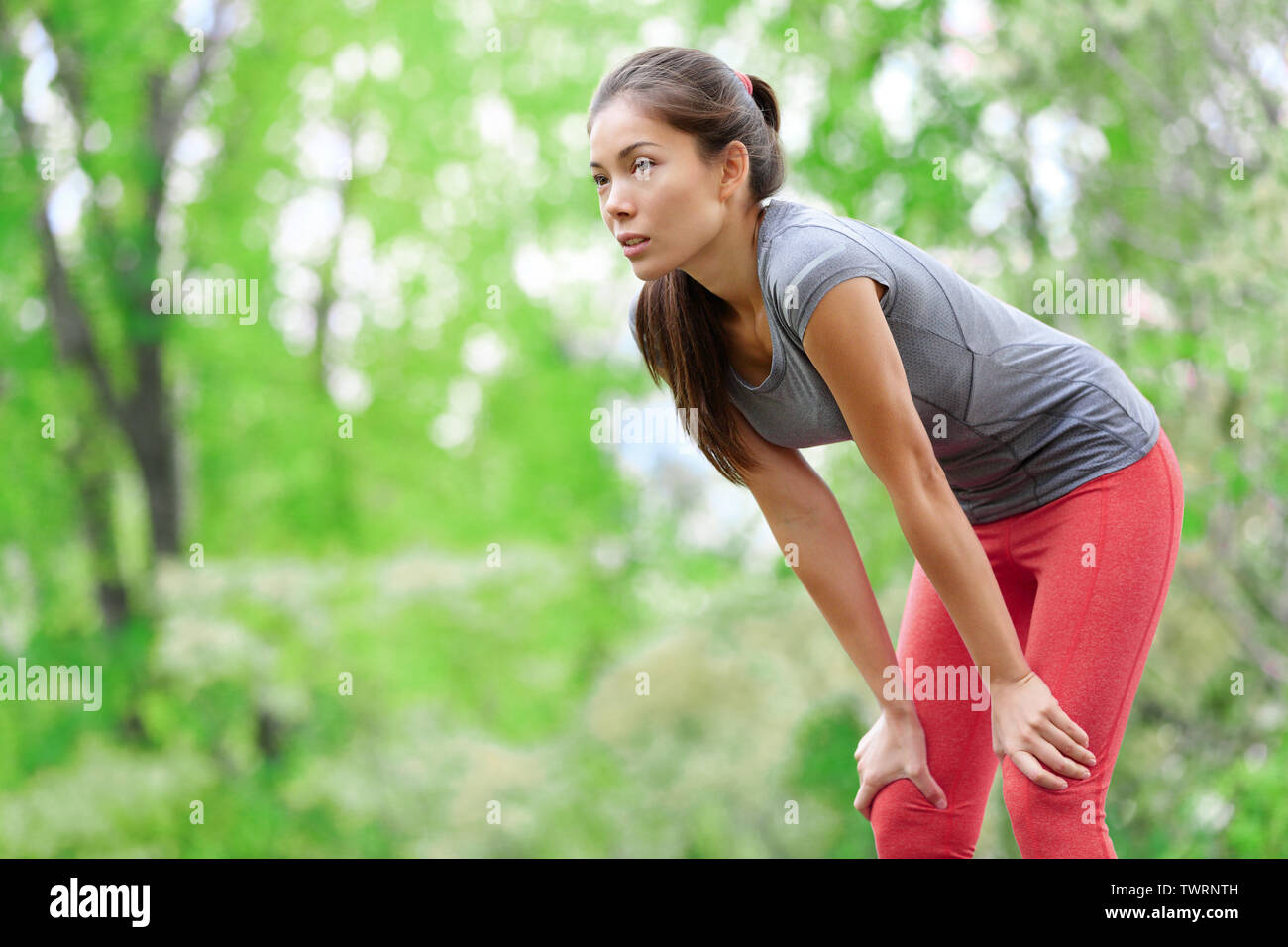 Asian woman athlete runner resting after running and jogging training outdoors in forest. Tired exhausted beautiful sports fitness model living healthy active lifestyle. Mixed race Asian Caucasian. Stock Photo