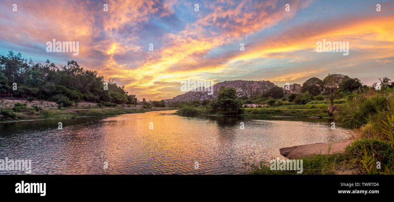 A view over a river at sunset in south India. - Stock Image