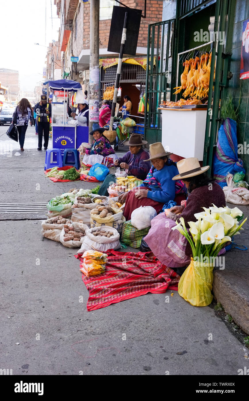 Huaraz, Ancash / Peru: 11 June 2016: indigent Indio farmer women sell their fruit and vegetables on the streets of Huaraz - Stock Image