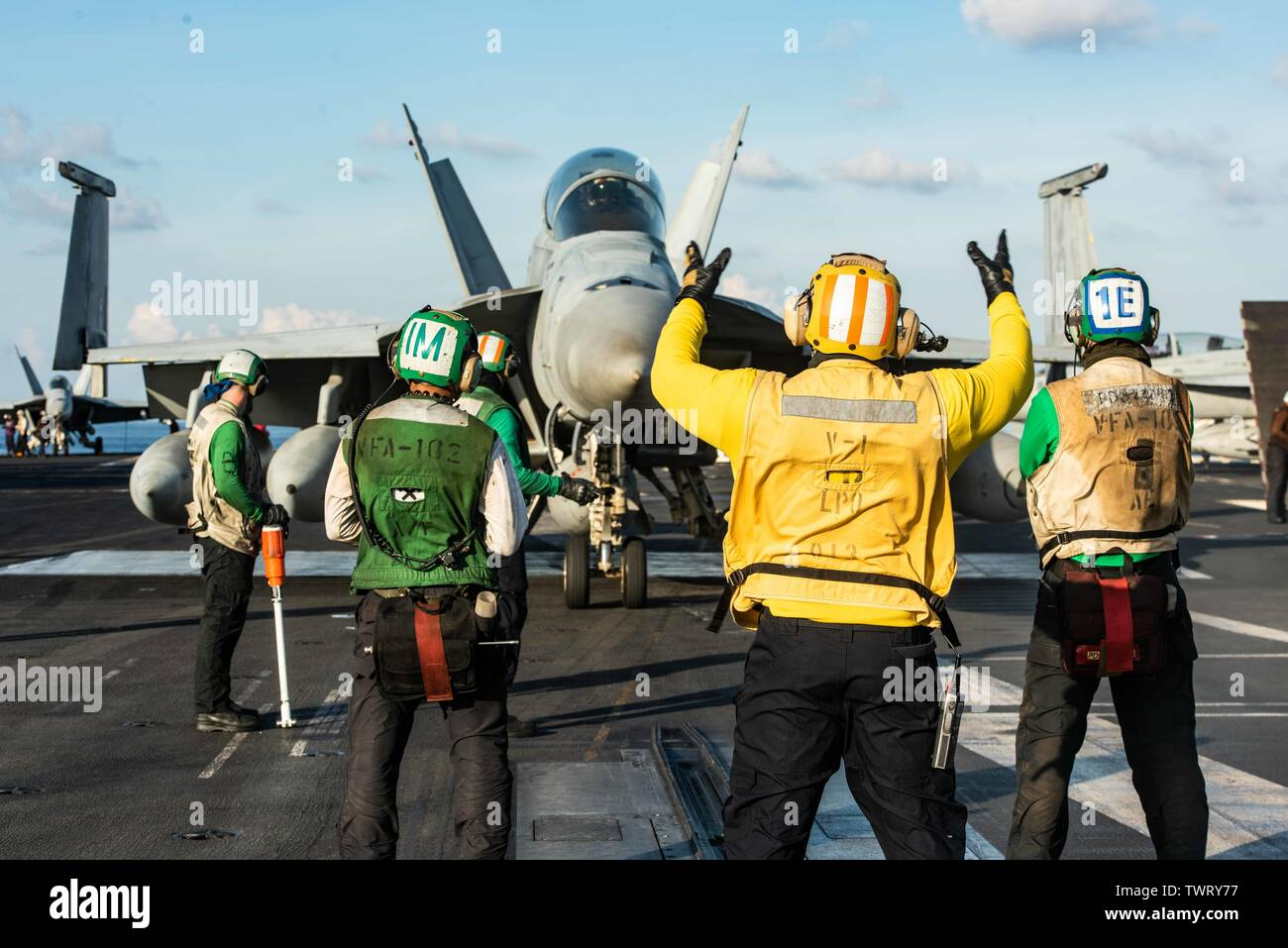 190620-N-CL027-2062  SOUTH CHINA SEA (June 20, 2019) Sailors direct the movement of an F/A-18F Super Hornet from Strike Fighter Squadron (VFA) 102 prior to launching on the flight deck aboard the Navy's forward-deployed aircraft carrier USS Ronald Reagan (CVN 76) during flight operations. Ronald Reagan, the flagship of Carrier Strike Group 5, provides a combat-ready force that protects and defends the collective maritime interests of its allies and partners in the Indo-Pacific region. (U.S. Navy photo by Mass Communication Specialist 2nd Class Janweb B. Lagazo/Released) - Stock Image