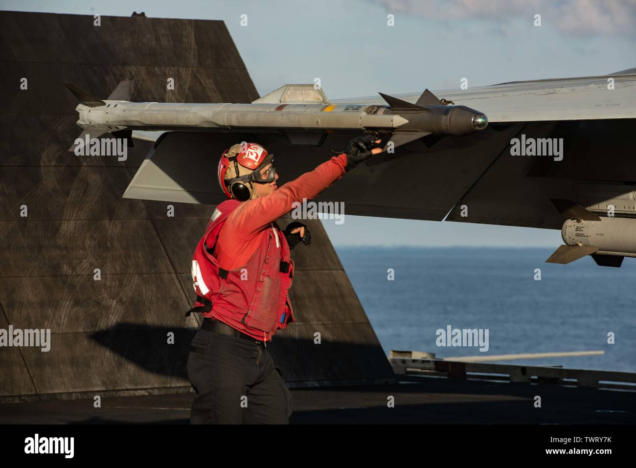 190620-N-CL027-2273  SOUTH CHINA SEA (June 20, 2019) An Aviation Ordnanceman inspects a seated missile on an F/A-18E Super Hornet from Strike Fighter Squadron (VFA) 115 prior to launch on the flight deck aboard the Navy's forward-deployed aircraft carrier USS Ronald Reagan (CVN 76) during flight operations. Ronald Reagan, the flagship of Carrier Strike Group 5, provides a combat-ready force that protects and defends the collective maritime interests of its allies and partners in the Indo-Pacific region. (U.S. Navy photo by Mass Communication Specialist 2nd Class Janweb B. Lagazo/Released) - Stock Image