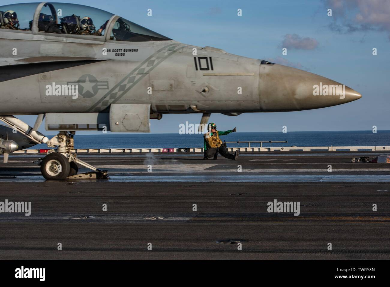 190620-N-CL027-2081  SOUTH CHINA SEA (June 20, 2019) Aviation Boatswain's Mate (Equipment) 3rd Class Shelbey Hochsmith, from Federalsburg, Maryland, signals all-clear to launch an F/A-18F Super Hornet from Strike Fighter Squadron (VFA) 102 on the flight deck aboard the Navy's forward-deployed aircraft carrier USS Ronald Reagan (CVN 76) during flight operations. Ronald Reagan, the flagship of Carrier Strike Group 5, provides a combat-ready force that protects and defends the collective maritime interests of its allies and partners in the Indo-Pacific region. (U.S. Navy photo by Mass Communicati - Stock Image