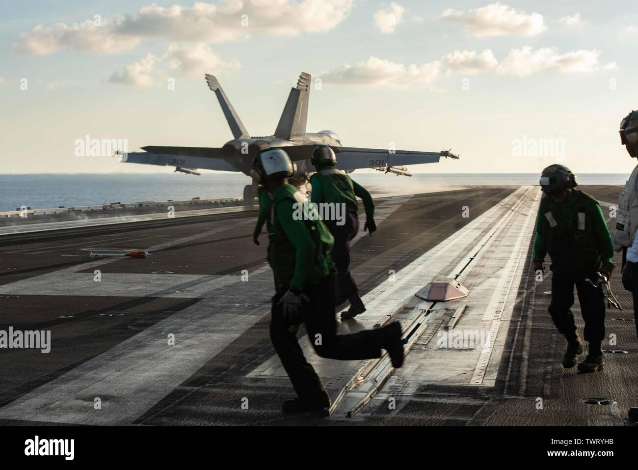 190620-N-CL027-2299  SOUTH CHINA SEA (June 20, 2019) Sailors run to retrieve the holdback bar on the flight deck aboard the Navy's forward-deployed aircraft carrier USS Ronald Reagan (CVN 76) during flight operations. The holdback bar is used to hold back the aircraft prior to its launch from the steam catapults. Ronald Reagan, the flagship of Carrier Strike Group 5, provides a combat-ready force that protects and defends the collective maritime interests of its allies and partners in the Indo-Pacific region. (U.S. Navy photo by Mass Communication Specialist 2nd Class Janweb B. Lagazo/Released - Stock Image