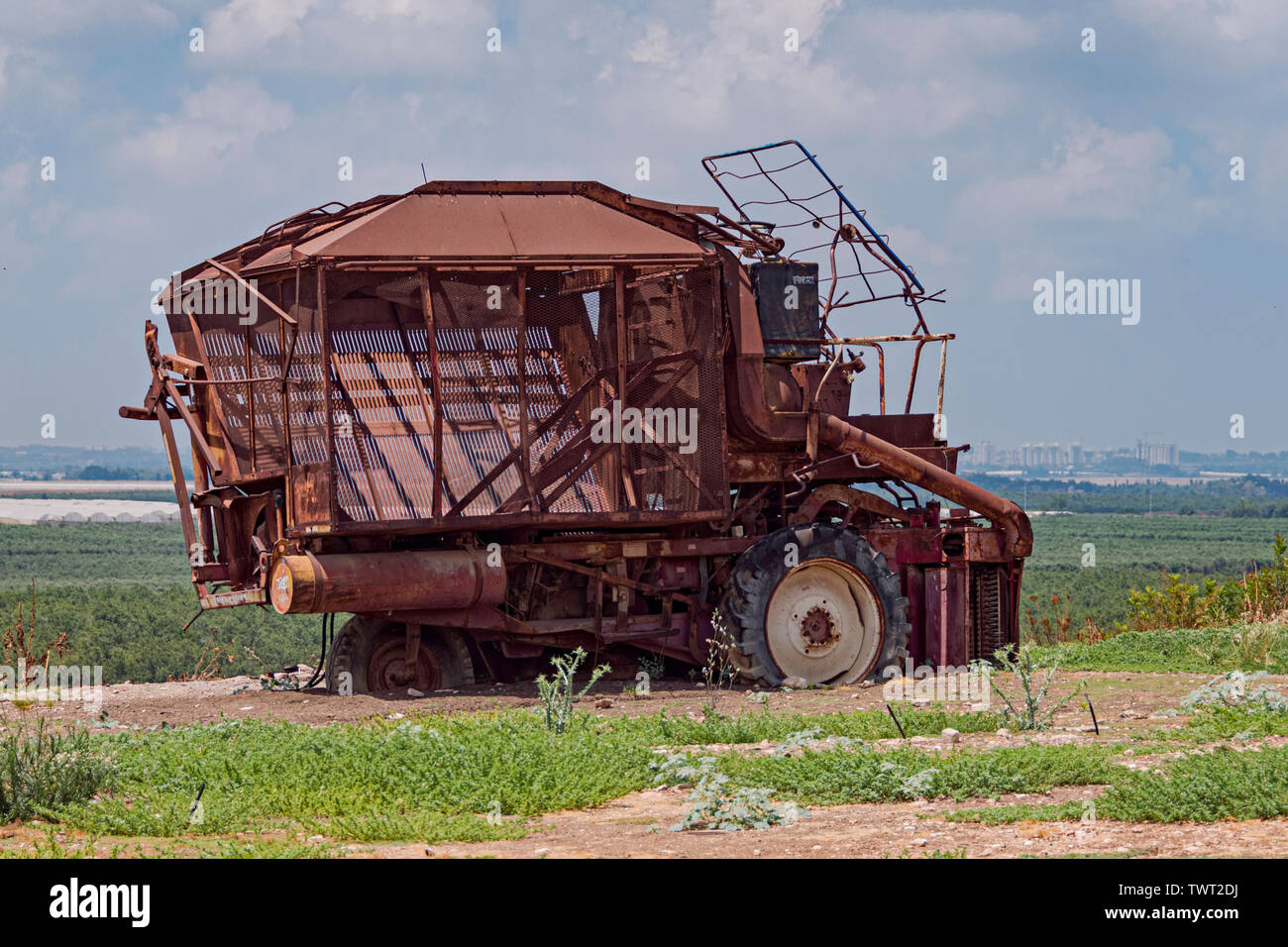 a broken down rusty old cotton picking machine sits above modern fields and greenhouses in israel with a palestinian city in the background - Stock Image