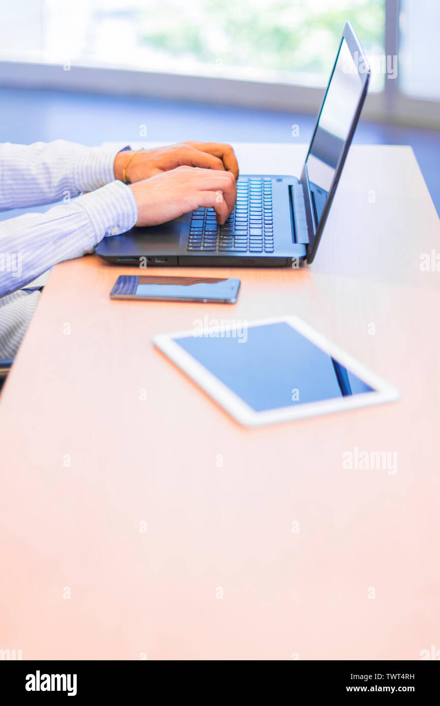 Businessman working at the office writing on his laptop with a smartphone and a digital tablet on the table - Stock Image