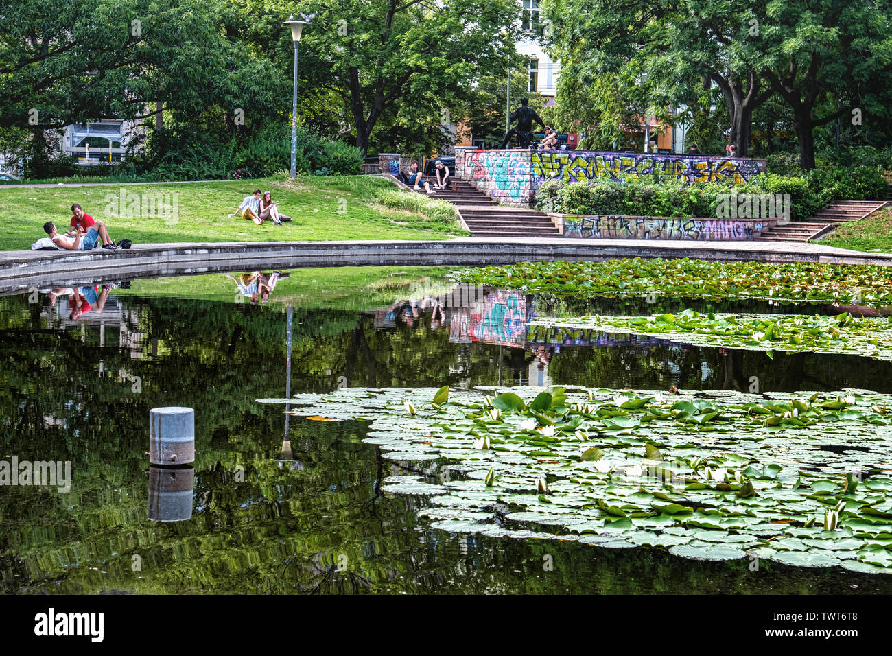 Volkspark am Weinberg Park, Mitte-Berlin. People relaxing next to pond in Summer. Young couple & reflections - Stock Image