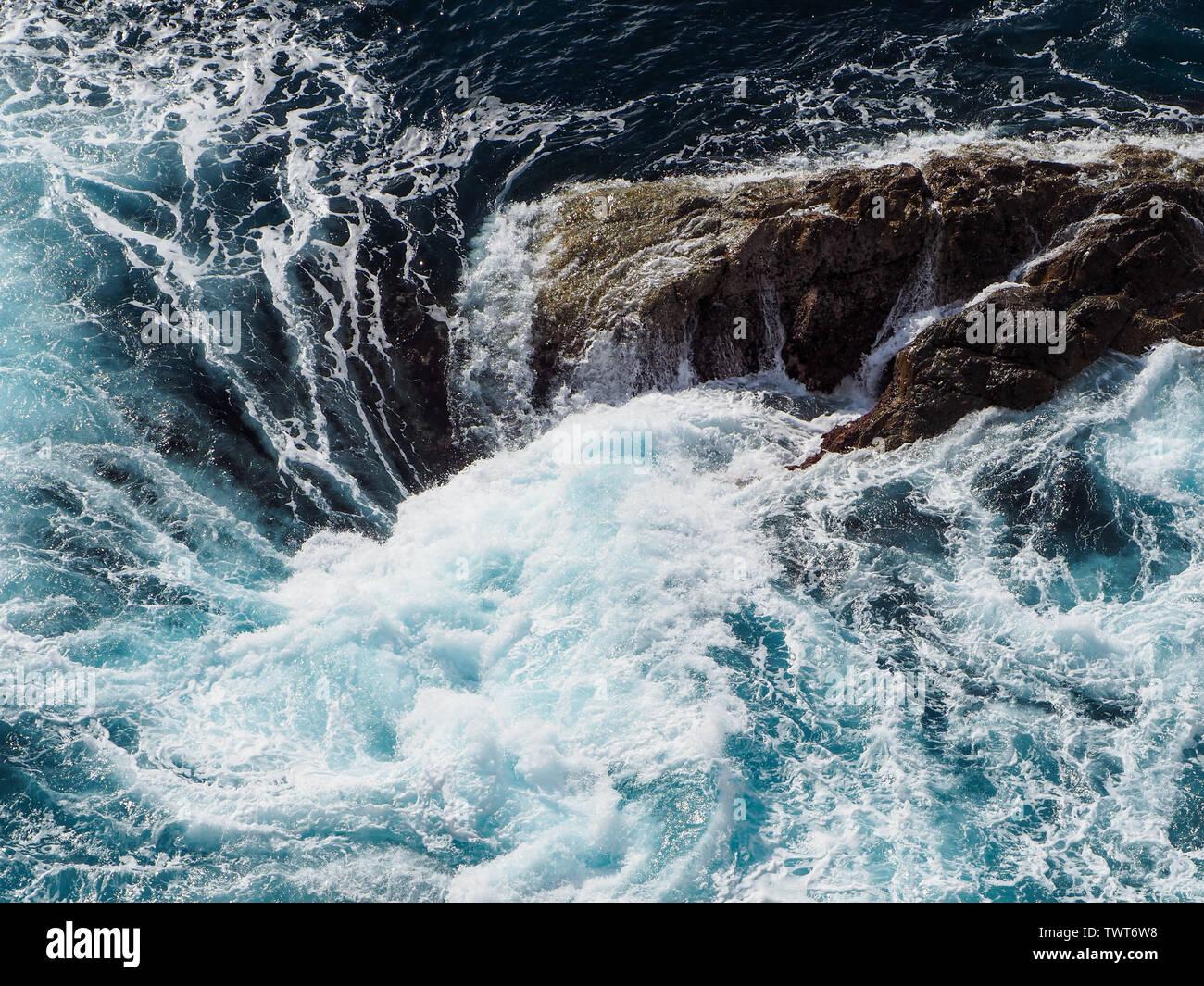 Sea water swirling around rocks Stock Photo