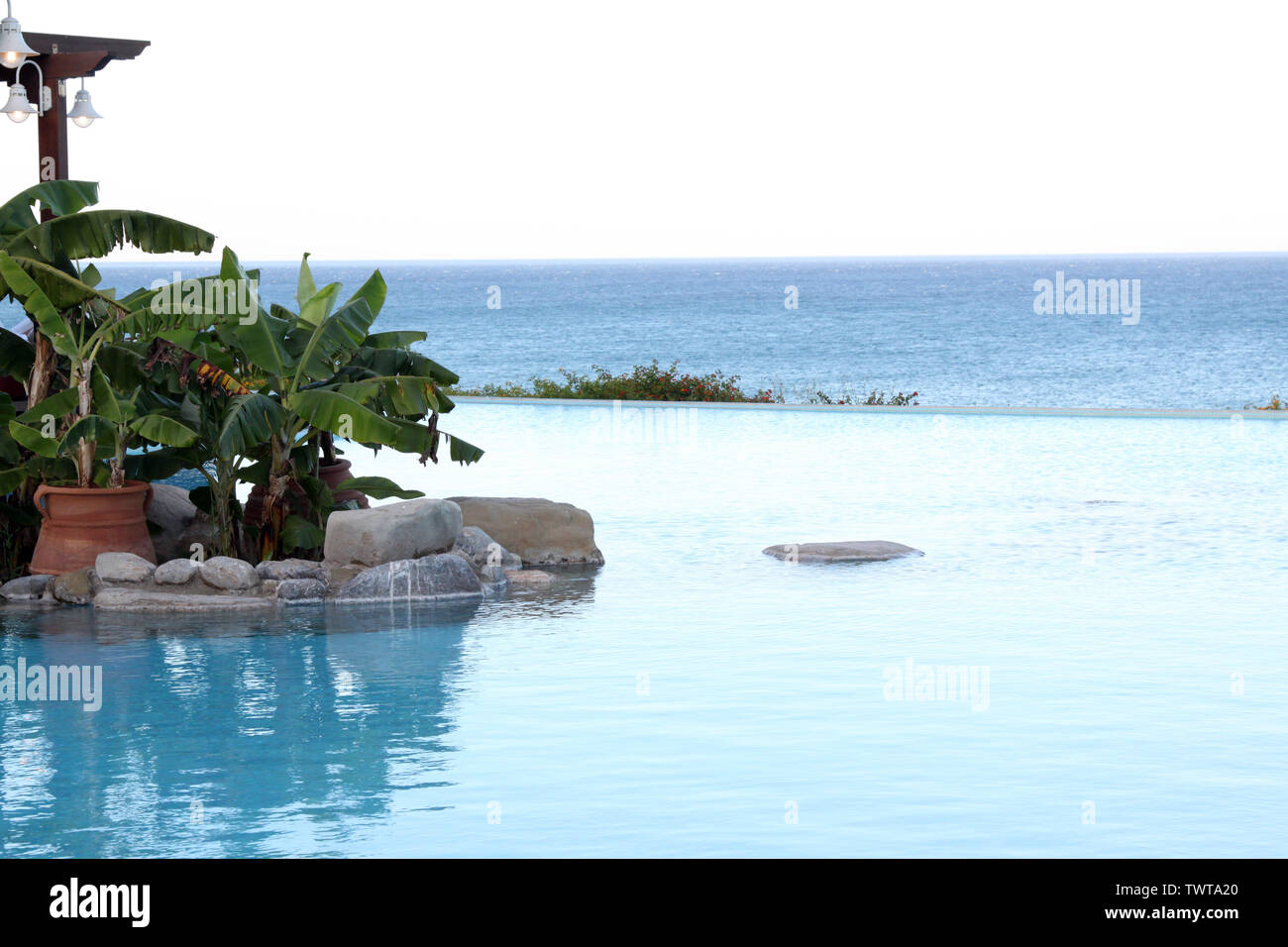 Rhodes, Greece - A view across hotel infinity pool with the sea in the background with blue white colour scheme, afternoon - Stock Image
