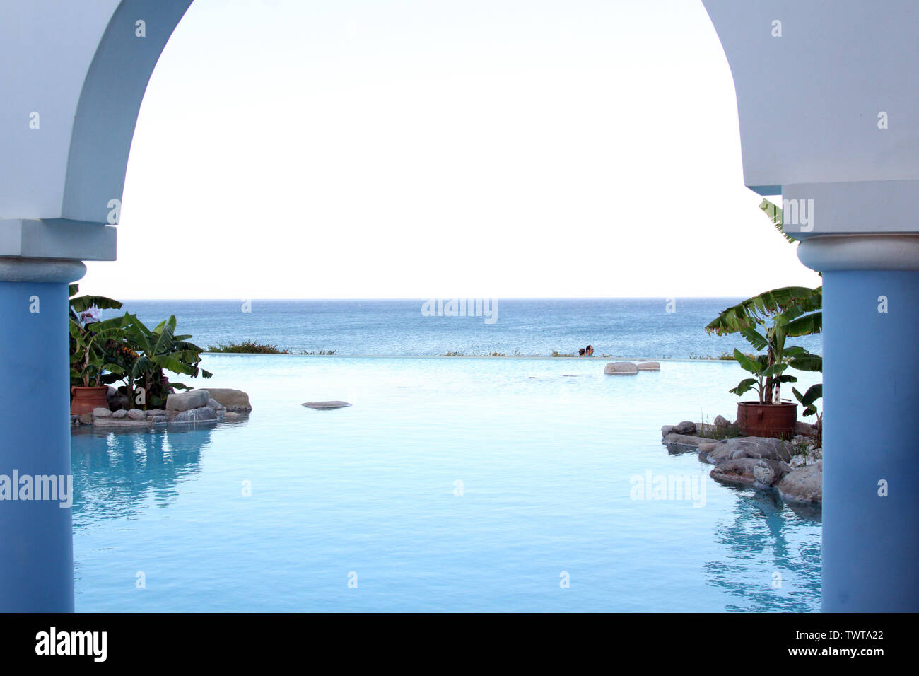 Rhodes, Greece - A view across hotel infinity pool with the sea in the background with blue white colour scheme, afternoon, framed with architecture - Stock Image
