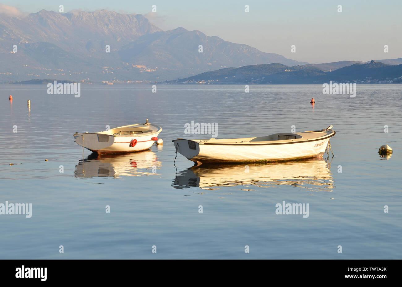 Empty fishermen's boats on Boka Kotorska Bay with Mount Lovcen in the background, Montenegro. Stock Photo
